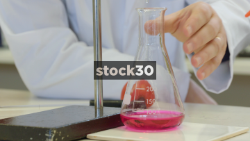 Slow Motion Shot Of Scientist Swirling Coloured Liquid In Conical Flask