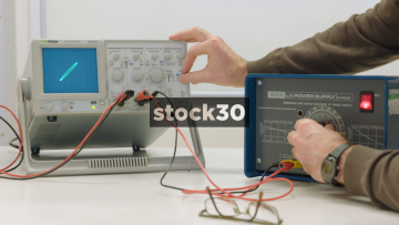 Scientist Adjusting Oscilloscope In Lab