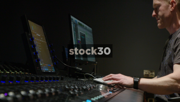 Man In Recording Studio Operating Avid S6 Control Surface