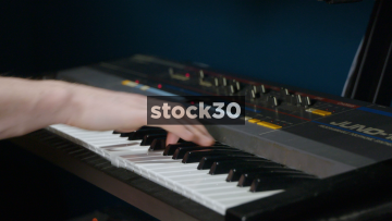 Close Up Shot Of Hands Playing Dual Keyboards In Recording Studio