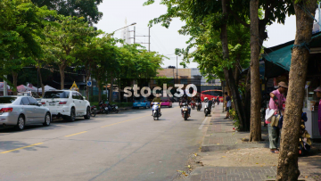 People And Traffic Passing On Phraya Mai Road In Bangkok, Thailand