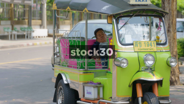 A Thai Man Asleep In A Tuk Tuk In Bangkok, Thailand