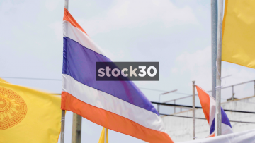 Slow Motion Shot Of The Thai Flag And The Dharmacakra Flag Of Buddhism In Bangkok, Thailand