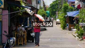 A Thai Lady Walking Down A Thai Side Street In Bangkok. Thailand