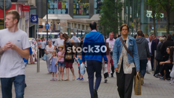 Slow Motion Shot Of Shoppers In Leeds, Including Men Using Sign Language, UK
