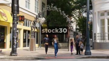 Pedestrians Crossing Near The S Truett Cathy Monument In Atlanta, USA