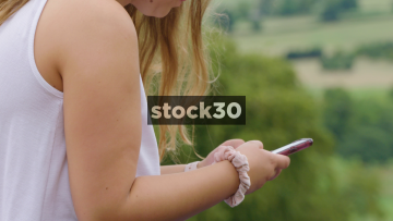 Young Woman Using Her Phone Overlooking The Cheshire Plain In Alderley Edge, UK