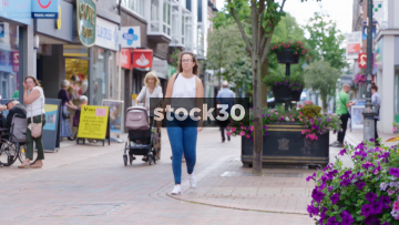 Young Woman Walking Into Monsoon Clothes Shop In Wilmslow, UK