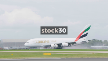 Emirates Airbus A380-861 Taxiing After Landing On A Wet Runway In Manchester With A Passing Lufthansa Airbus A321-231 Taking Off, UK