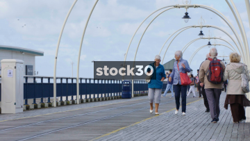 Slow Motion Shot Of Pensioners Walking Along Southport Pier, UK