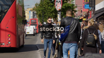 Slow Motion Shot Of Camden High Street With People, Buses And Taxis, UK