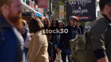 Slow Motion Shot Of People Passing By Market Stalls On Camden High Street, UK