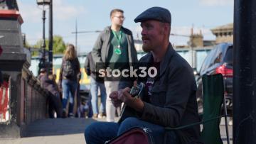Busker Playing Guitar On Camden High Street, UK