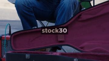 Close Up Shot Of Busker Playing Guitar On Camden High Street, UK