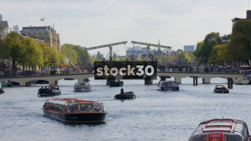 Boats On The Amstel River In Amsterdam. Magere Brug In Background, Netherlands