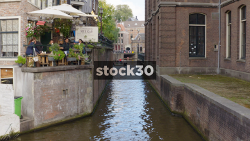 Boat Passing Down Narrow Section Of The Rokin Canal In Amsterdam, Netherlands