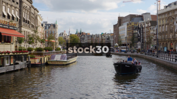 Three Cruise Boats On The Rokin Canal In Amsterdam, Netherlands