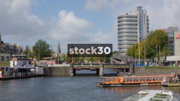 Tram Crossing Bridge Over River In Amsterdam, Netherlands