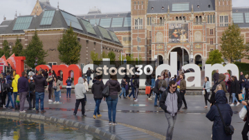 Wide Shot Of Tourists At The I Amsterdam Sign With the Rijksmuseum In Background, Netherlands