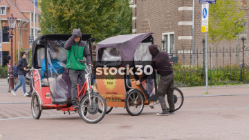 Two Bicycle Taxis Departing At The Rijksmuseum In Amsterdam, Netherlands