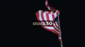 Slow Motion Shot Of The USA Flag Flying At Night, USA