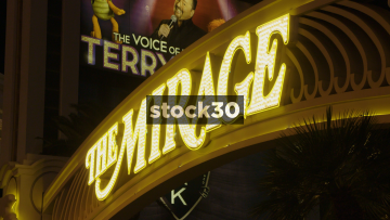 Pedestrians Passing By The Sign For The Mirage Hotel And Casino In Las Vegas, USA