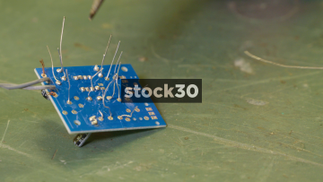Man Soldering Electronic Components Onto A Printed Circuit Board