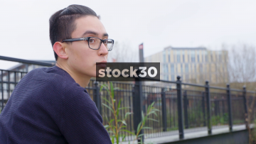Young Man In A Contemplative Mood Standing By Bridge