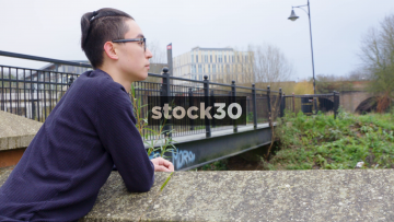 Slow Zoom Into Contemplative Young Man Standing By Bridge
