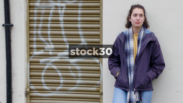 Serious Looking Young Woman Leaning Against Wall