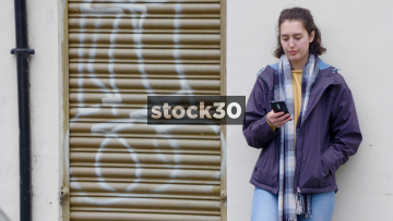 Young Woman Standing By Wall Making A Phone Call To A Friend
