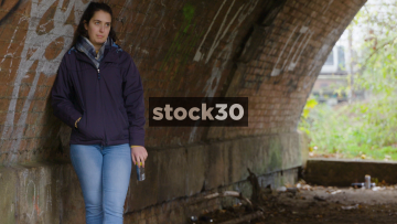 Unemployed Young Woman Standing Under Bridge With Drinks Can