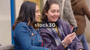 Two Young Women Chatting While Looking At Photos On A Smartphone