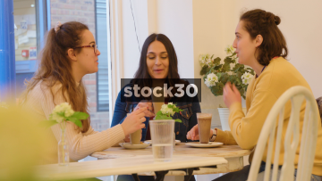 Three Young Women Having Coffee And Chatting In A Cafe - Wide Shot