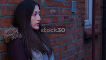 Wide Shot Of Depressed And Worried Young Woman Leaning Against A Wall