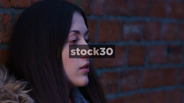 Slow Motion Shot Of Depressed And Worried Young Woman Leaning Against A Wall
