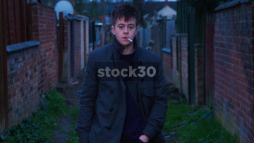 Slow Motion Shot Of Young Man Smoking Cigarette In Alleyway
