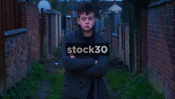 Slow Motion Shot Of Young Man With Arms Folded Smoking Cigarette In Alleyway