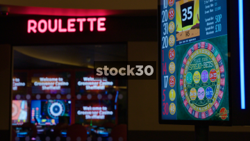 Electronic Betting Board And Neon Roulette Sign In Casino