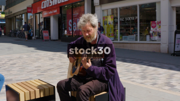 Busker Playing Guitar In Shrewsbury, Wide Shot, UK