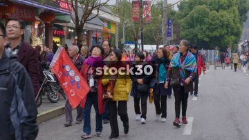 Group Of Tourists Passing By On Foyou Road In Shanghai, China