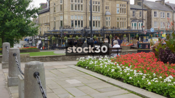 Old Couple Sitting On Bench In Harrogate With Betty's Cafe Tea Rooms In Background, UK