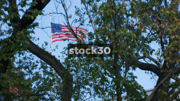 Slow Motion Shot Of US Flag Viewed Through Trees In Lafayette Square, Washington DC, USA