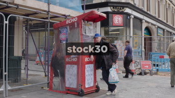 Liverpool Echo Newspaper Stand With Passing Pedestrians, UK