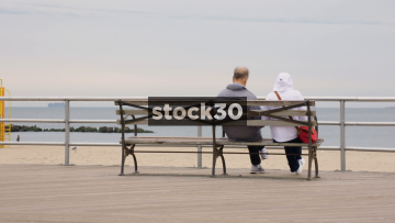 Old Couple Sitting On Bench Looking Out To Sea At Coney Island, Brooklyn, New York, USA