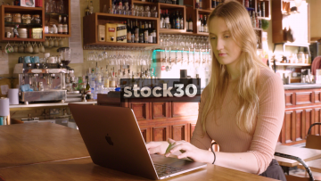 Girl Using Apple MacBook Pro Laptop In Bar, Wide Shot
