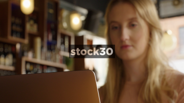 Girl Using Apple MacBook Pro Laptop In Bar, Focus Pull To Face