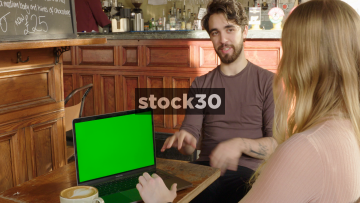 Young Couple Having Conversation In Coffee Shop With Apple Macbook Pro Computer And Green Screen