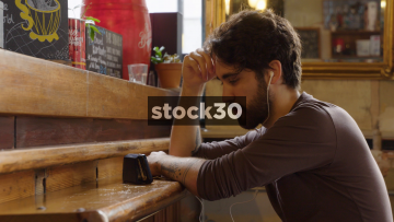 Man In Bar Watching Content On Smart Phone With Headphones In