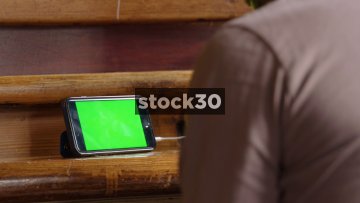 Man In Bar Watching Content On Smart Phone, Close Up On Phone With Green Screen